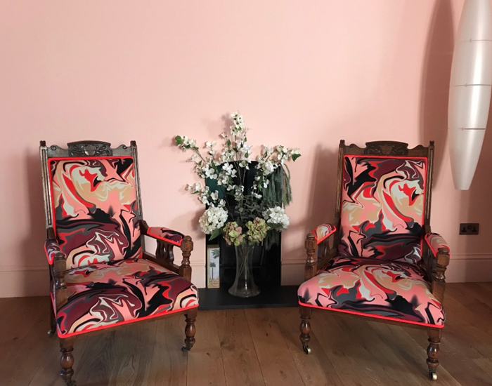 Two chairs on wheels reupholsterd in patterned pink velvet