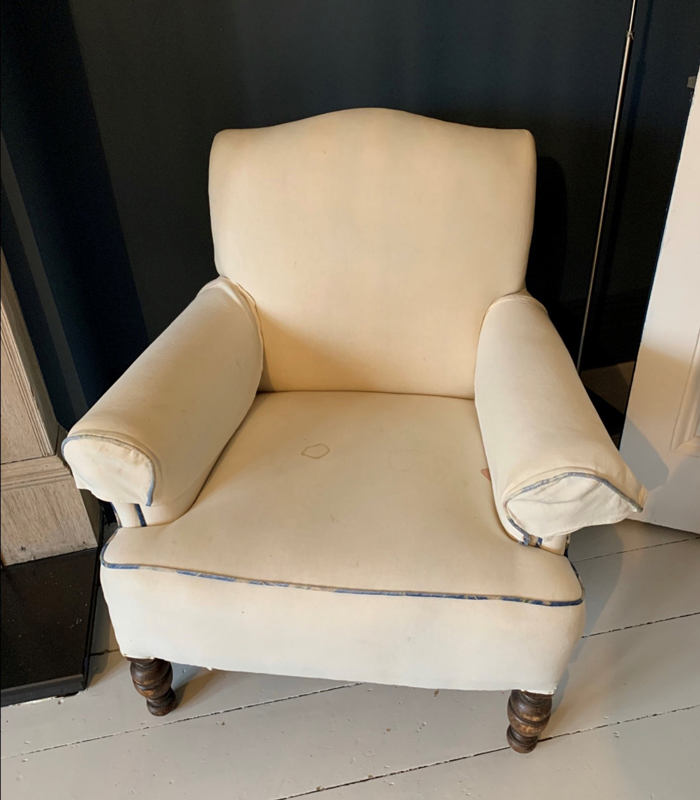 White armchair in need of reupholstering