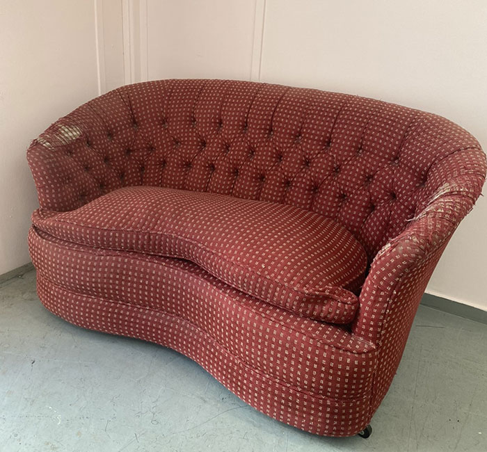Old red patterned sofa in need of reupholstering