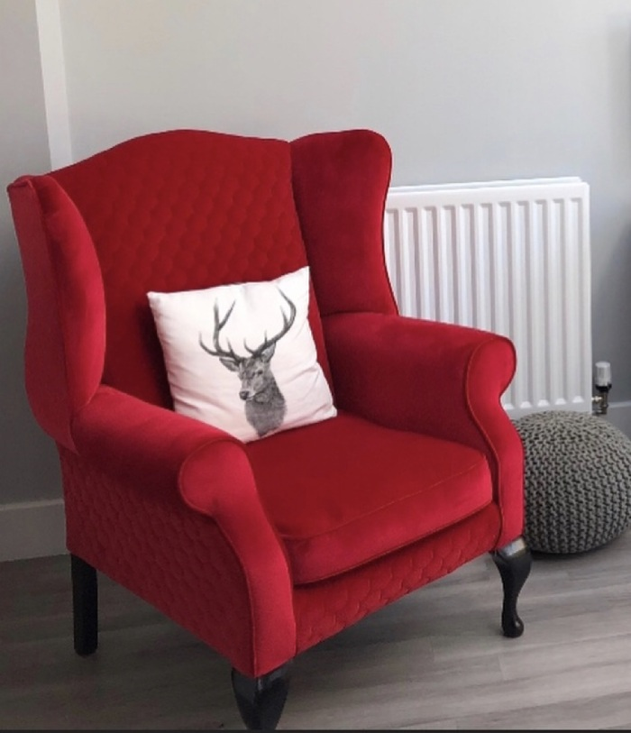 Red reupholstered armchair