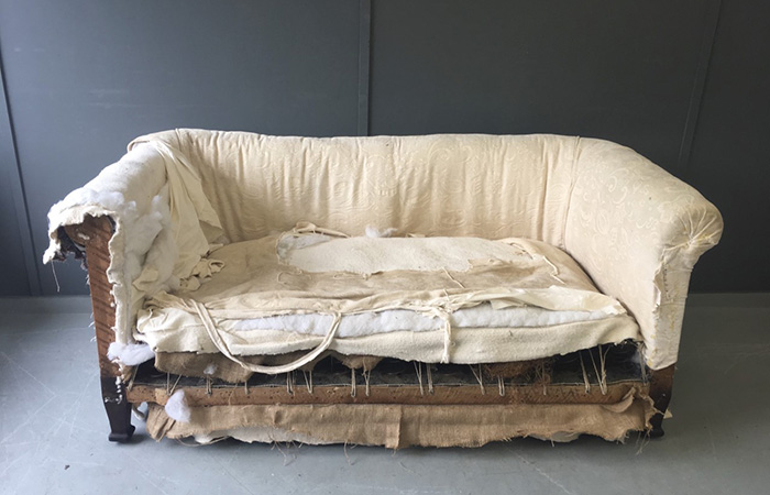 Old sofa undergoing upholstery project in the workshop