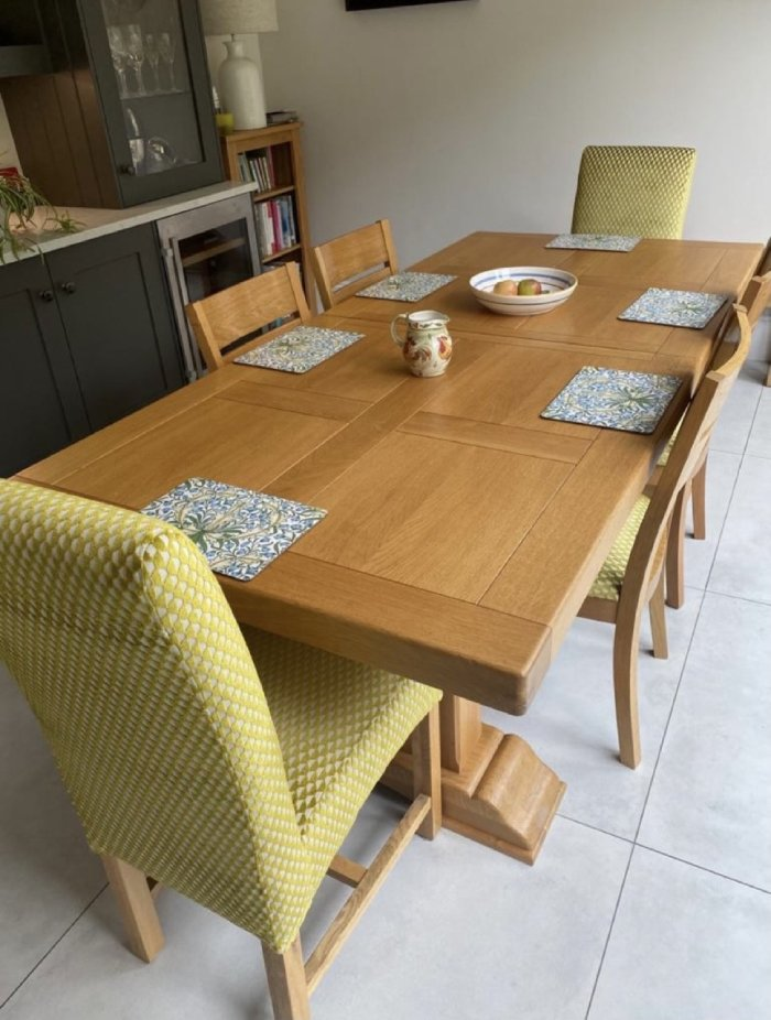 Lime green reupholstered chairs around wood dining room table
