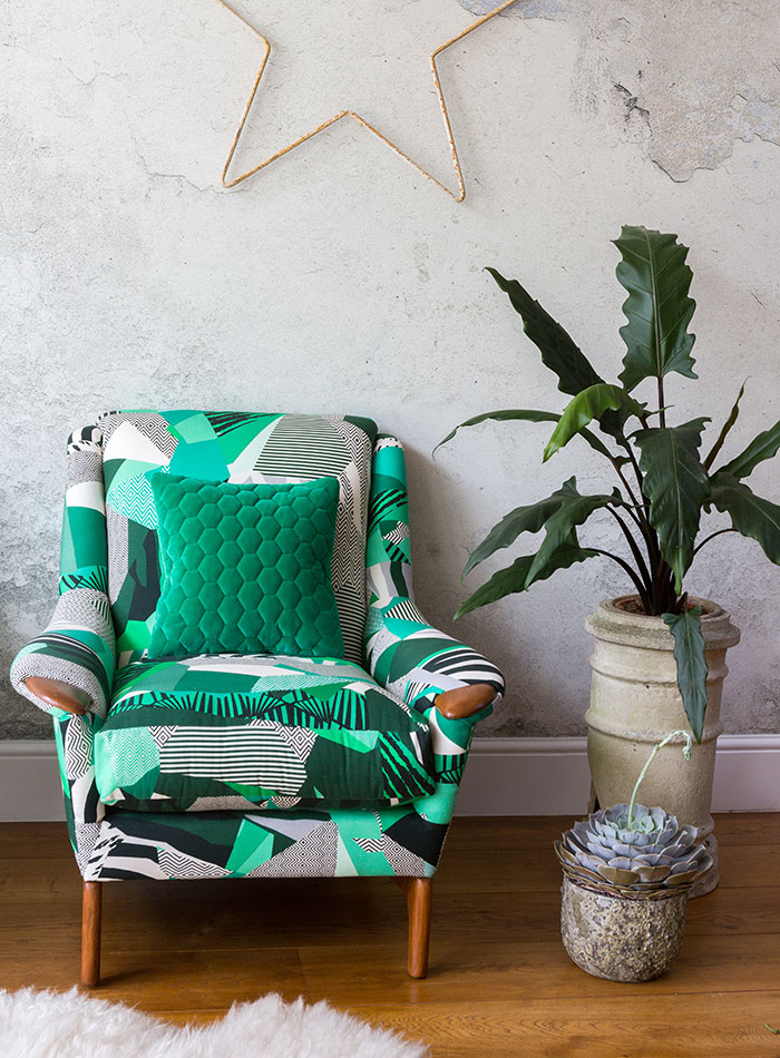 Reupholstered green patterned armchair against concrete background