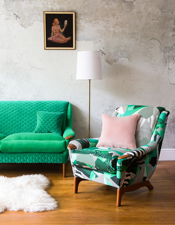 Reupholstered green sofa and patterned armchair against concrete background