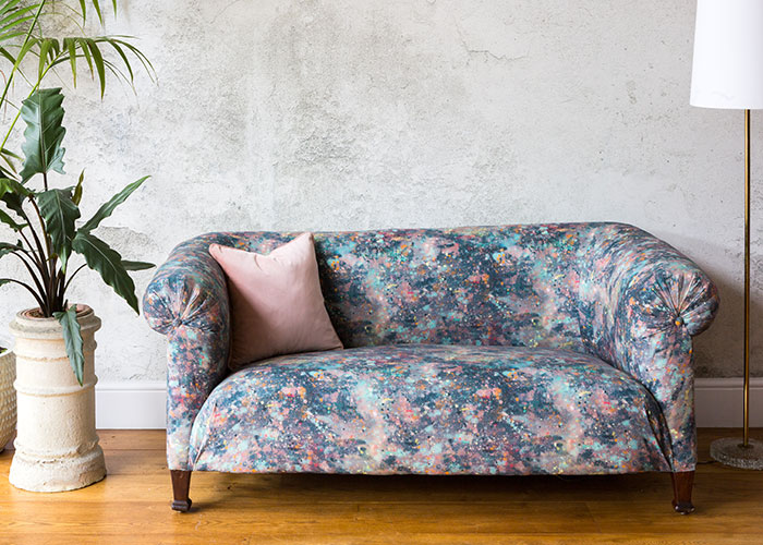 Reupholstered patterned chesterfield sofa against concrete background