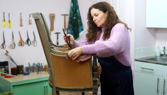 Sharon O'Connor reupholstering an armchair in workshop